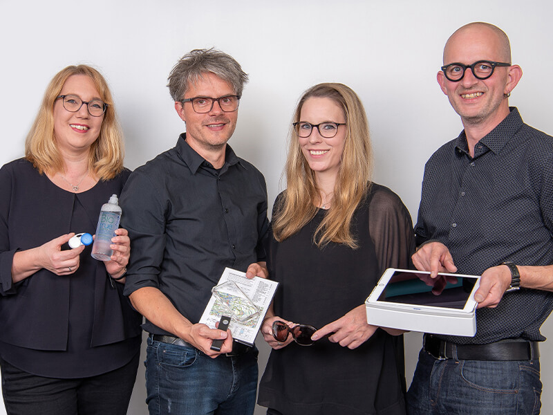 Tibarg Center Optik Ruge Teamfoto mit diversen Produkten