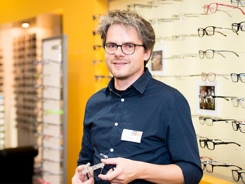 Tibarg Center Optik Ruge Verkäufer vor Wand mit Brillen