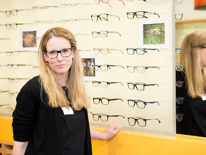 Tibarg Center Optik Ruge Verkäuferin vor Wand mit Brillen